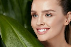 Natural Cosmetics. Beautiful Woman Face With Green Plant. Natural Cosmetics. Beautiful Woman Face With Healthy Skin And Green Plant On Jungle Background. High stock photo