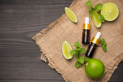 Natural cosmetics for home spa. Bottle of essence oil with fresh. Limes royalty free stock image