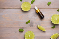 Natural cosmetics for home spa. Bottle of essence oil with fresh. Limes royalty free stock photos