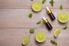 Natural cosmetics for home spa. Bottle of essence oil with fresh. Limes stock images