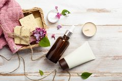 Natural cosmetics with lilac flowers. Serum, soap and cream with towel rolls. Face care products. Prepare to bath. Spa therapy concept photo. Organic cosmetic royalty free stock image
