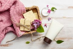 Natural cosmetics with lilac flowers. Set of cream and towel rolls. Face care products. Prepare to bath. Spa therapy concept photo. Organic cosmetic on wooden stock photography