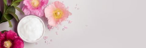 Natural Cosmetics product, flavored sea salt and mallow flowers. On gray background. Toned. Banner long format Stock Images