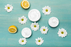 Natural cream in containers, chamomiles and sliced lemon on blue wooden table Royalty Free Stock Photography