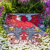Natural Crest, Emblem, Flag of City Meran in flowerbed and vegetation. Merano. Province Bolzano, South Tyrol, Italy. Europe royalty free stock photo