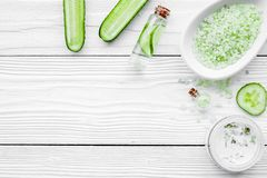 Natural cucumber cosmetics. Lotion, cream, spa salt on white wooden background top view copyspace Royalty Free Stock Images