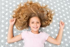 Natural curls treat and care. Girl child with long curly hair lay on bed top view. Child perfect curly hairstyle looks. Cute. Conditioner mask organic oil keep Royalty Free Stock Images