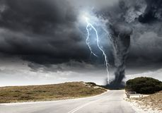 Natural disaster. Powerful tornado and lightning above countryside road Stock Photo