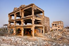 After a natural disaster - ruined buildings. Landscape of ruined buildings at sunset, image of decrepitude or natural disaster Stock Photos