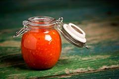 Natural diy habanero garlic sauce. Homemade DIY natural hot pepper - habanero and garlic sauce on a beautiful green wooden table Royalty Free Stock Photography