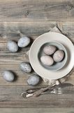 Natural dyed grey Easter eggs. Natural dyed gray Easter eggs with plates and silverware on rustic grey wooden background. Top view point Stock Image