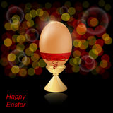 Natural easter egg on a stand with a red bow on a dark background. Royalty Free Stock Photo