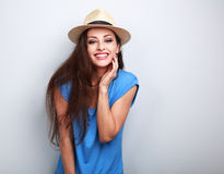 Natural emotional laughing woman in summer hat looking happy. On blue background Stock Image