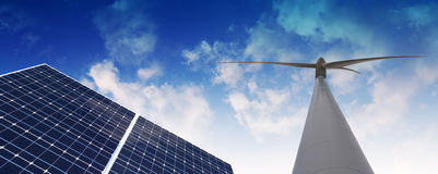 Natural energies. Solar panel and wind mill against cloudy sky Royalty Free Stock Image