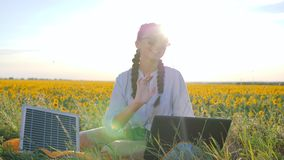 Natural energy, happy young woman applying solar photovoltaic panels outdoors, female in backlight with notebook. Charging from sun, girl recharges laptop using stock video