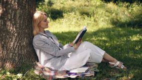 Natural environment office. Work outdoors benefits. Online dream job. Student studying in a park. Minute for relax. Girl. Work with notebook in park sit on stock footage