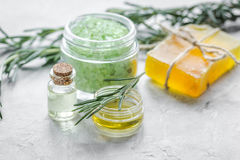 Natural essential aroma oil with rosemary on stone table background. Natural homemade essential aroma oil, soap and salt with rosemary on aged stone table stock photography