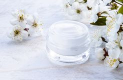Natural face cream with spring flowers, cherries. Face cream stock photos