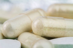 Natural food supplement pills, glucosamine capsules and calcium, macro image, soft blurred background. Stock Photos