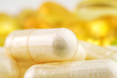 Natural food supplement pills, glucosamine and omega 3 capsules, macro image. Royalty Free Stock Photography