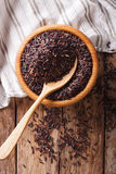 Natural Foods: Raw wild black rice close up in a wooden bowl. Ve Stock Photo