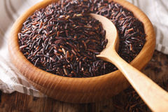 Natural Foods: Raw wild black rice macro in a wooden bowl. Horiz Royalty Free Stock Photography