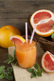 Natural and fresh grapefruit juice in glass with freshly harvested grapefruit stock photography