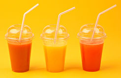 Natural Fruit Juices in orange background Royalty Free Stock Photos