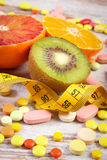 Natural fruits, centimeter and medical pills, slimming, choice between healthy nutrition and medical supplements. Fresh natural fruits, tape measure, pills Royalty Free Stock Photography