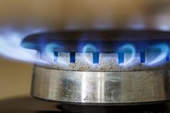 Natural gas blue flames burns on the kitchen stove hob, close up Stock Photo