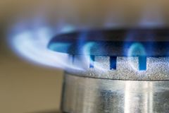 Natural gas blue flames burns on the kitchen stove hob, close up Stock Image