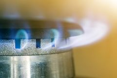 Natural gas blue flames burns on the kitchen stove hob, close up photo with shallow DOF.  stock photos