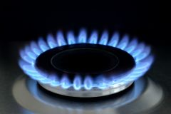 Natural gas burning on kitchen gas stove on black. Natural gas burning on kitchen gas stove. Panel from steel with a gas ring burner on a black background, Macro royalty free stock photography