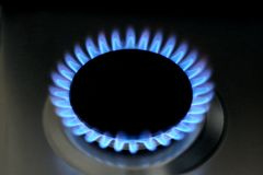 Natural gas burning on kitchen gas stove on black. Natural gas burning on kitchen gas stove. Panel from steel with a gas ring burner on a black background, Macro royalty free stock photo