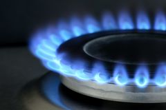 Natural gas burning on kitchen gas stove on black stock photography