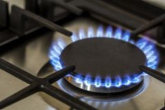 Natural gas burning on kitchen gas stove in the dark. Panel from steel with a gas ring burner on a black background, close-up shoo stock images