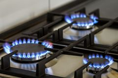 Natural gas burning on kitchen gas stove in the dark. Panel from stock images