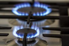 Natural gas burning on kitchen gas stove in the dark. Panel from steel with a gas ring burner on a black background, close-up shoo royalty free stock photography
