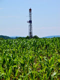 Natural Gas Drill Rising Out of Cornfield. Vertical shot of natural gas drill rising out of cornfield over Marcellus Shale natural gas deposit stock photography
