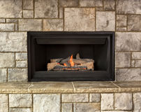 Natural gas fireplace for home. Burning natural gas fireplace surround by stone Royalty Free Stock Image