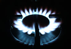 Natural gas flame on stove. Blue natural gas flame on stove burning at a stove`s eye Stock Photo
