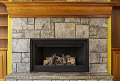 Natural Gas Insert Fireplace with Stone and Wood Stock Image