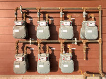 Natural gas meter bank on outside building wall. Bank of individual residential natural gas meters on building exterior to measure household consumption Stock Photos