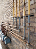 Natural Gas Pipes. A bunch of natural gas pipes on the side of  a building, connected to meters Royalty Free Stock Photos