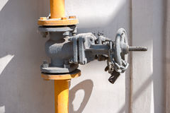 Natural gas valve on steel pipe painted in yellow with shadows Royalty Free Stock Photo