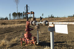 A natural gas wellhead. With many flanges, bolts, gauges, tubing Stock Photos