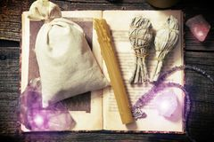 Natural rocks and white sage witchcraft tools. Natural gemstones, white sage, candle, sack on a book on wooden board, witchcraft tools Stock Photos