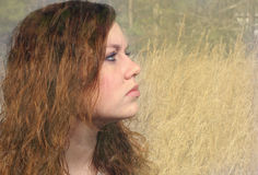 Natural girl. Profile of a pretty girl's face imposed on a field Royalty Free Stock Photography