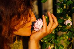 Natural girl holding a rose flower in a gentle gesture. royalty free stock photography