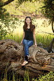 Natural girl sitting on tree. Pretty girl in natural setting sitting on tree Royalty Free Stock Image